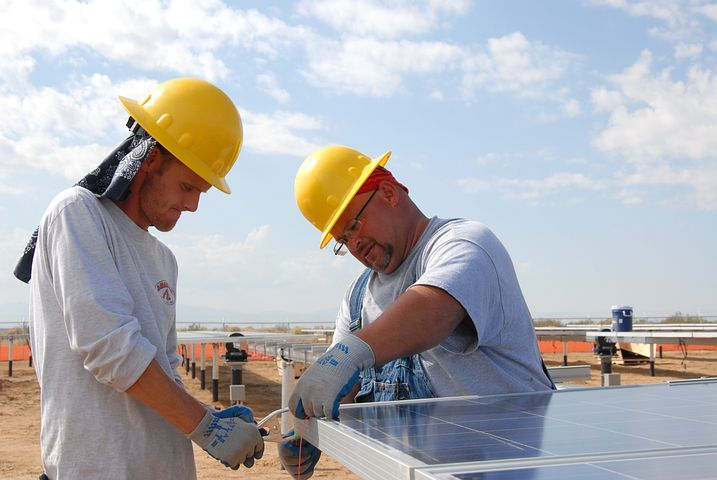 two men installing commercial solar panels